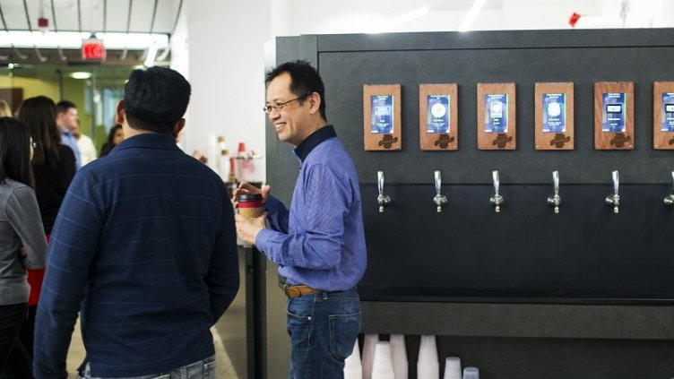 Man taking coffee from Machine and discussing with others